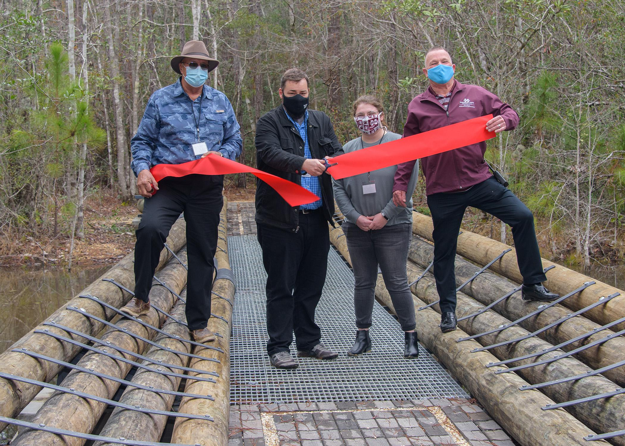 Four people stand on a bridge while cutting a ceremonial ribbon.