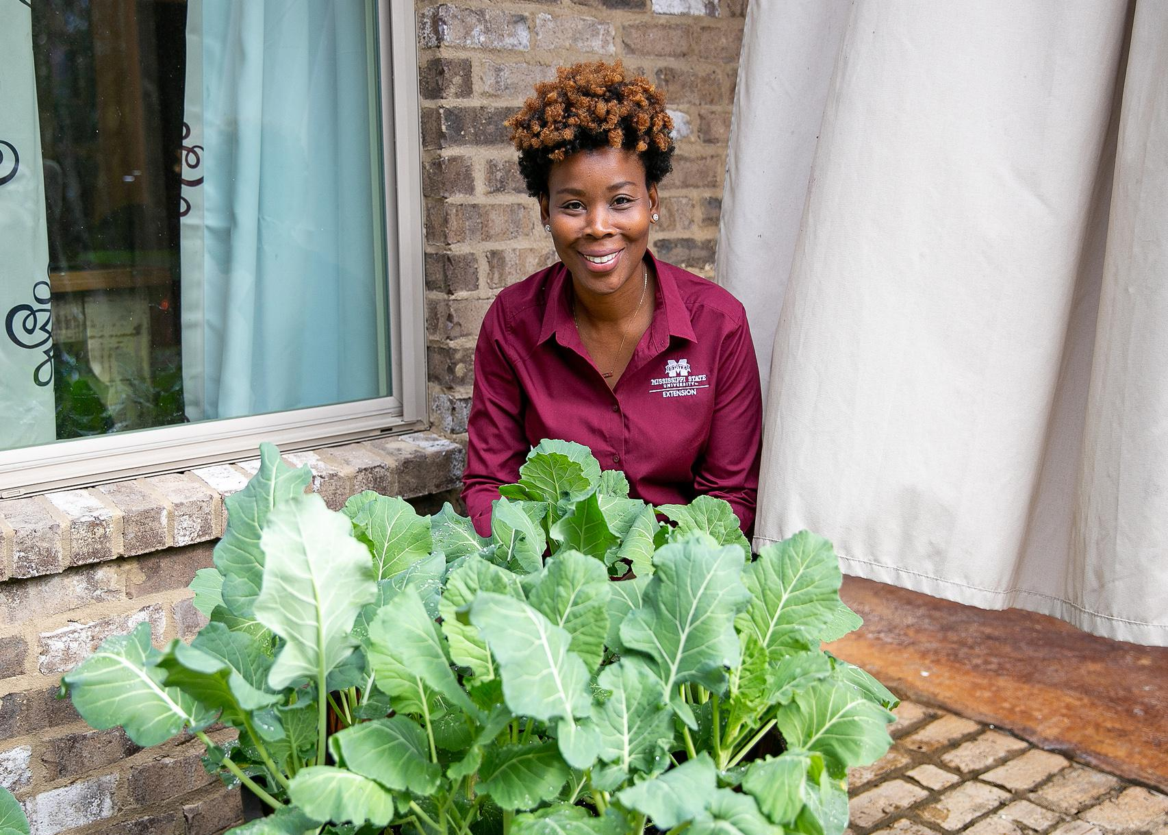 A woman sits on a patio behind a container where greens are growing.