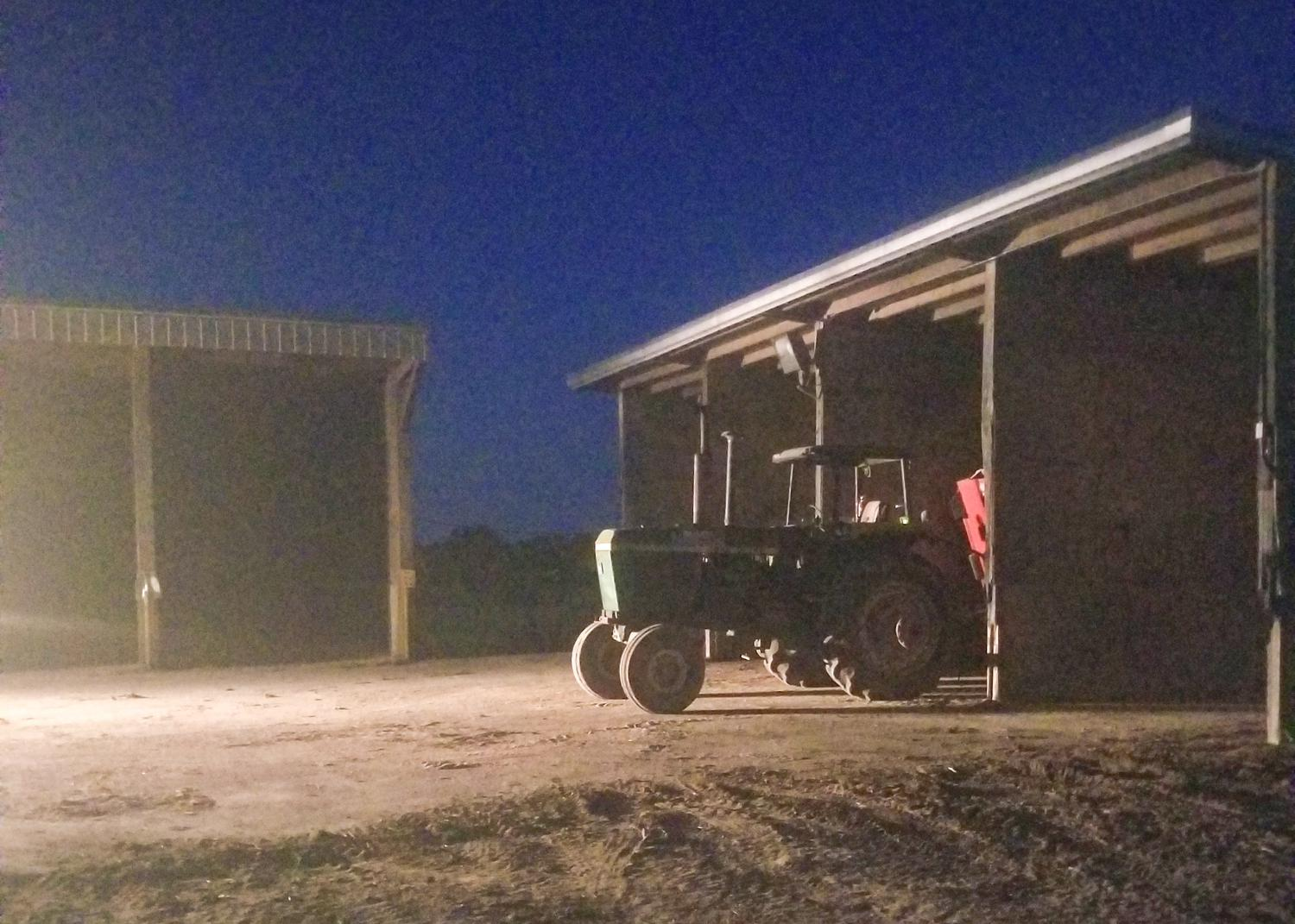 A tractor parked outside of a shed at night.
