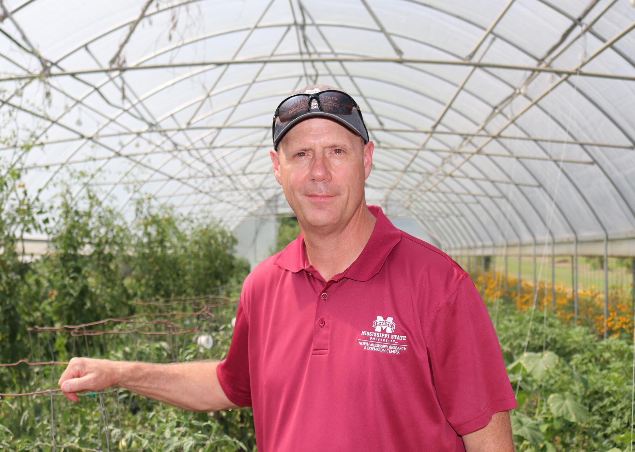 Man in a maroon shirt and baseball cap in a greenhouse.