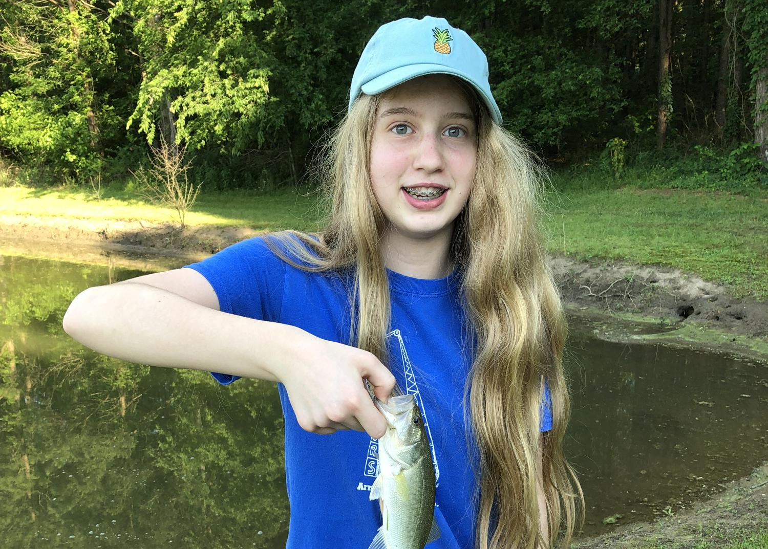 Girl in a blue T-shirt and baseball cap holding a small fish.