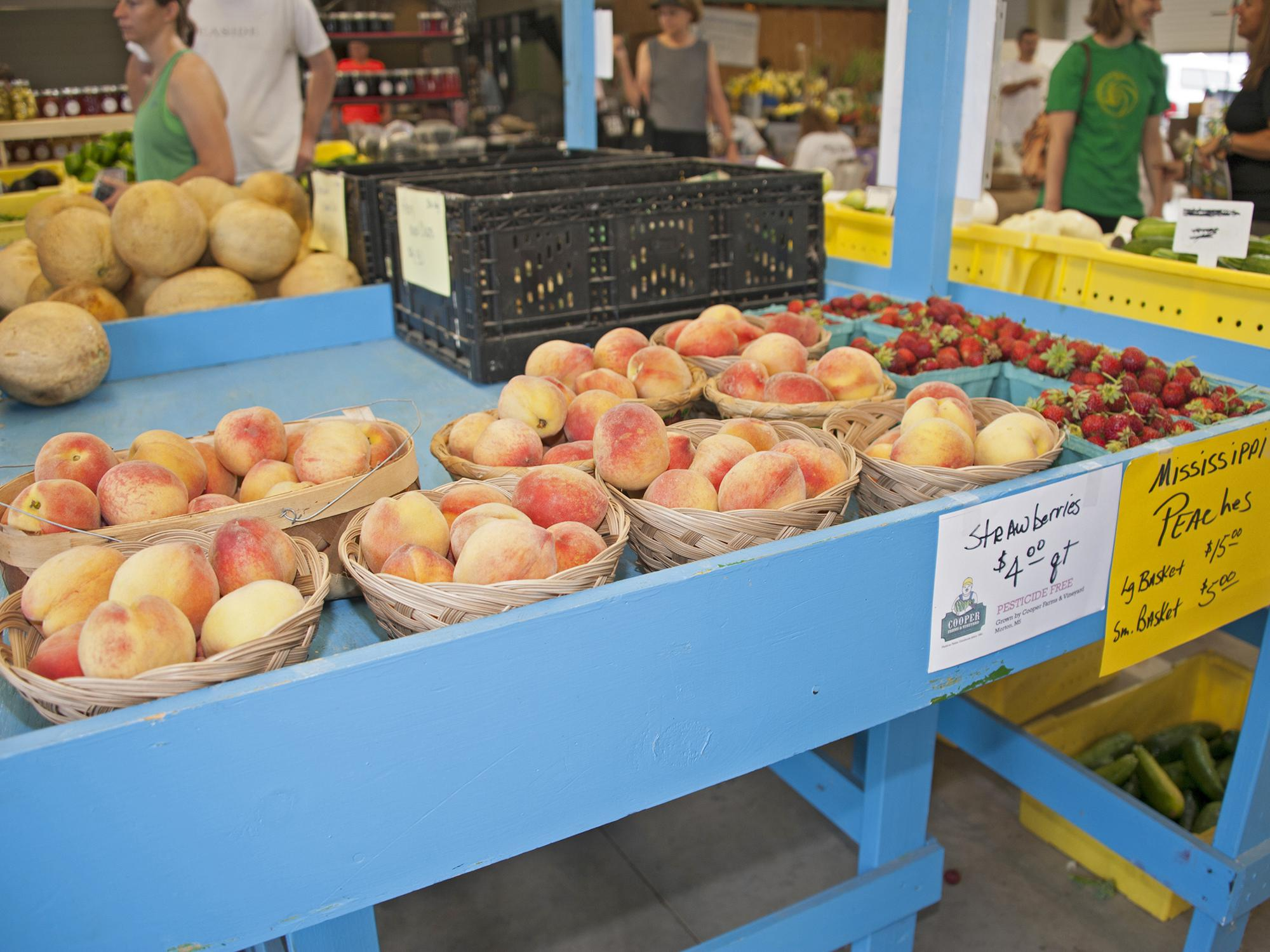 Peaches displayed for sale on a bright blue table. Production and sale of peaches, strawberries and other fruit and vegetable truck crops are on pace to be strong once again this year. (File photo by MSU Extension/Kat Lawrence)