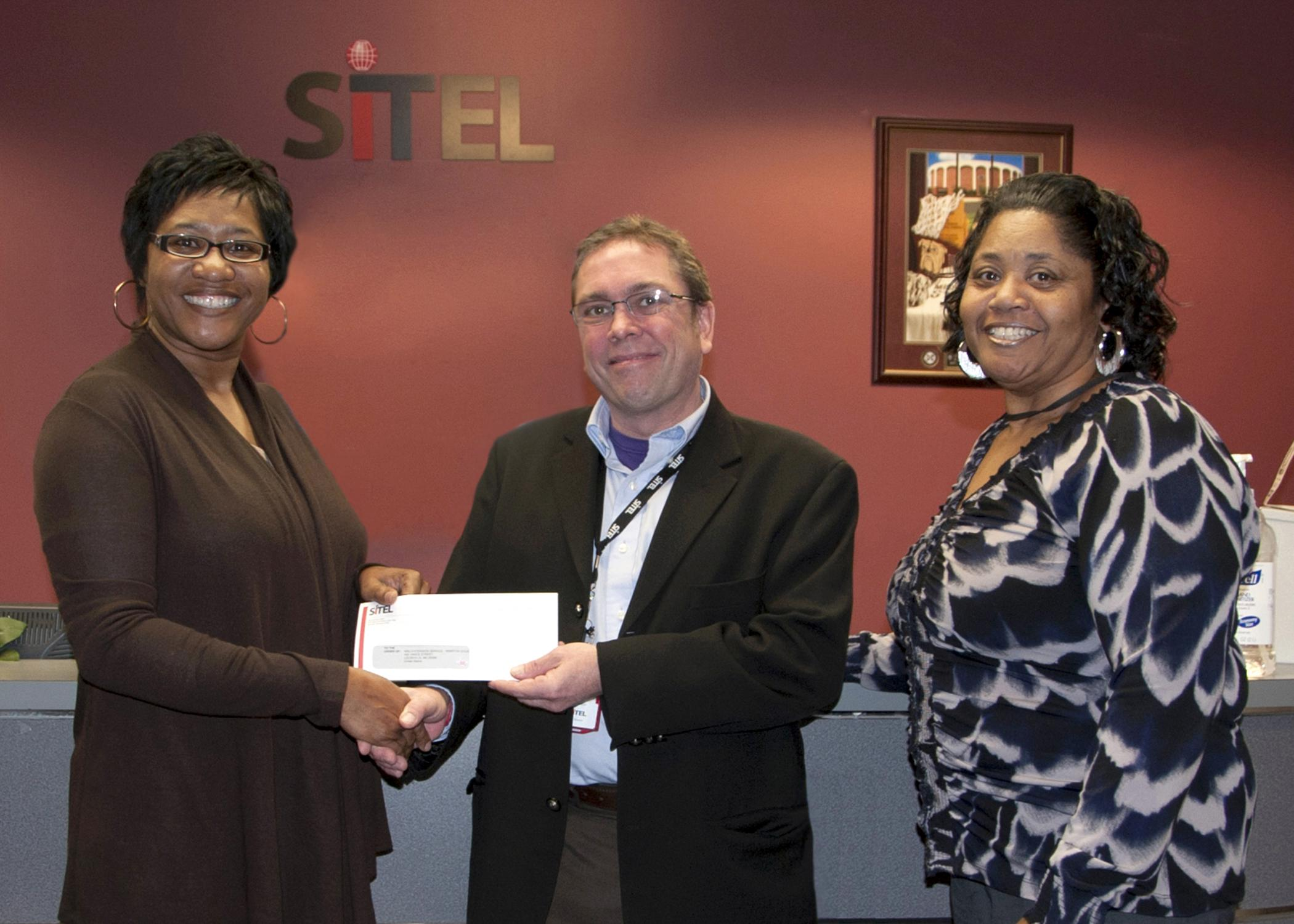 Sandra Jackson, left, a Mississippi State University Extension Service program associate, accepts a check from Dave Billington, Sitel Starkville site director, on behalf of Sitel's employee recognition program. Stella Jackson, right, Sitel's 2012 International Customer Management Institute Supervisor of the Year, chose to support the Winston County 4-H Youth Development program through Sitel's recognition program because of the positive impact it has on local youth. (Photo by MSU Ag Communications/Kat Lawre