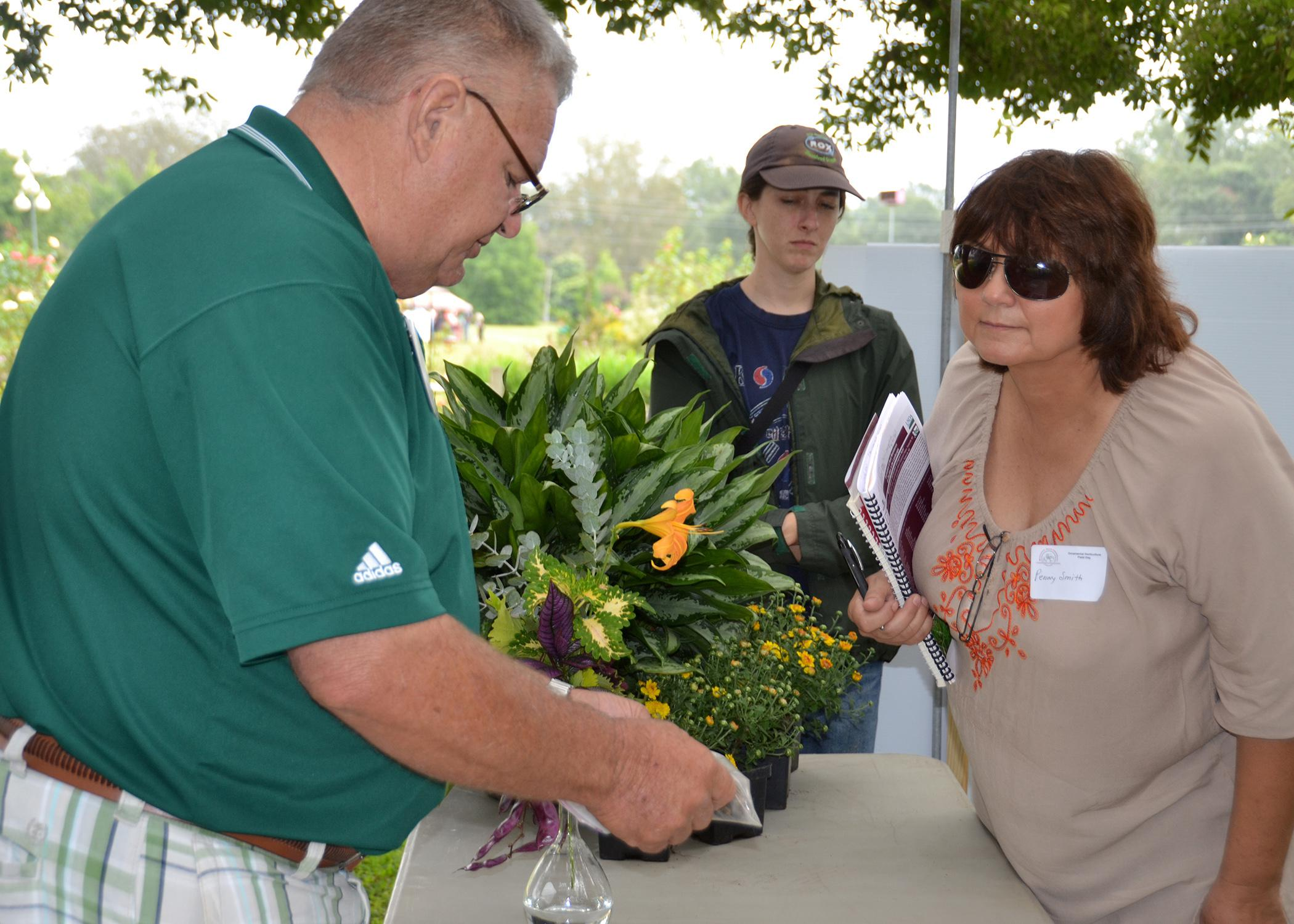 John Michael Anderson, a research associate with the Mississippi Agricultural and Forestry Experiment Station, explains propagating daylilies from seed to Penny Smith during the Ornamental Horticulture Field Day Oct. 10 at Mississippi State University's South Mississippi Branch Experiment Station in Poplarville. Leisure gardeners and horticulture industry professionals learned about the latest research findings, new plant varieties and helpful technologies. (Photo by MSU Ag Communications/Susan Collins-Smit