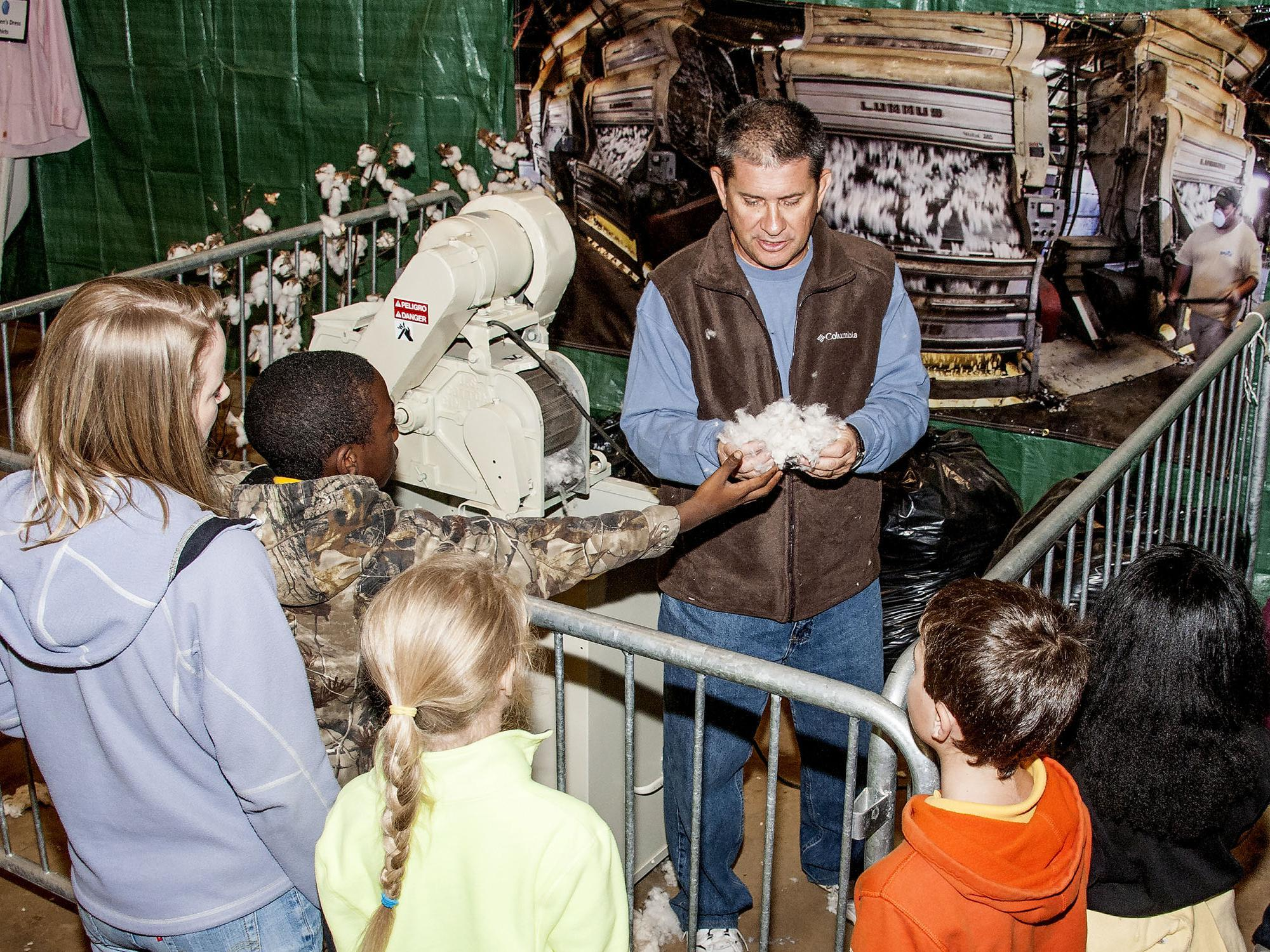 Dennis Reginelli, an area agronomic crops agent with the Mississippi State University Extension Service, explains the ginning process that helps create cotton fabrics. Addressing primarily third-graders at the Mississippi Horse Park on Nov. 7, 2013, Reginelli and the cotton exhibit were part of Farmtastic, a four-day educational program designed to help children learn the sources of their food, clothing and other products. (Photo by MSU Ag Communications/Scott Corey)
