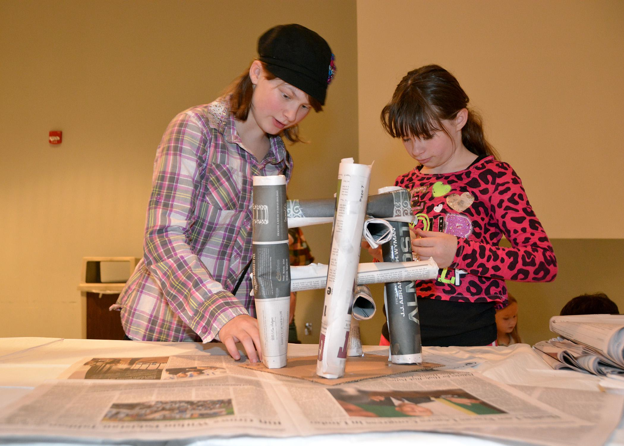 Lisa Cain, 11, and Mary Jane Cain, 10, use rolled-up newspaper to build a paper table at the Mississippi State University Mechanical Engineering Service Learning Showcase Nov. 20. 4-H members tested educational projects developed by MSU students in partnership with MSU's Center for the Advancement of Service-Learning Excellence. (Photo by MSU Ag Communications/Bonnie Coblentz)