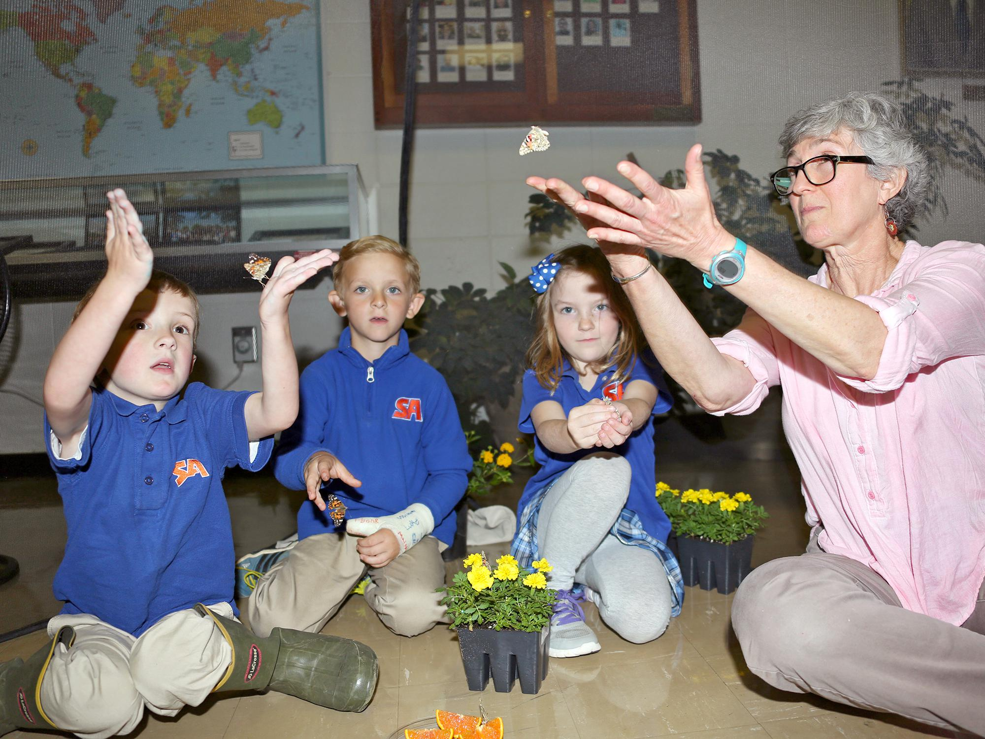 From left, kindergarteners Garrison Baker, Knox Smith and Piper Graves learn about painted lady butterflies with Lois Connington, keeper of the Insect Zoo at Mississippi State University's Clay Lyle Entomology Building on Thursday, April 14, 2016 in Starkville, Miss. (Photo by MSU Extension Service/Kat Lawrence)