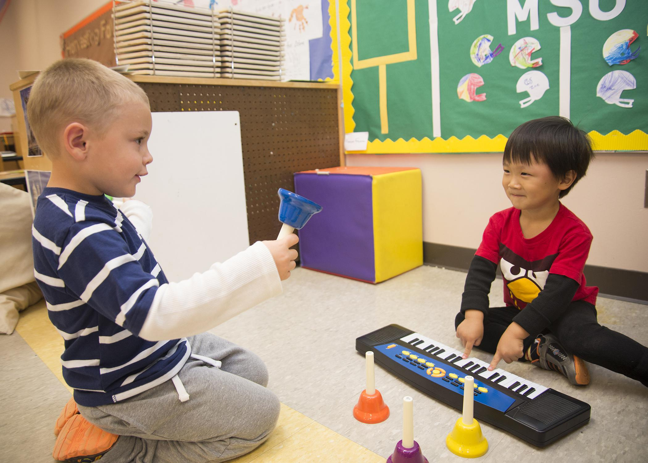 These two preschoolers play their first musical instruments in the Child Development and Family Studies Center at Mississippi State University. (School of Human Sciences file photo/Alicia Barnes)