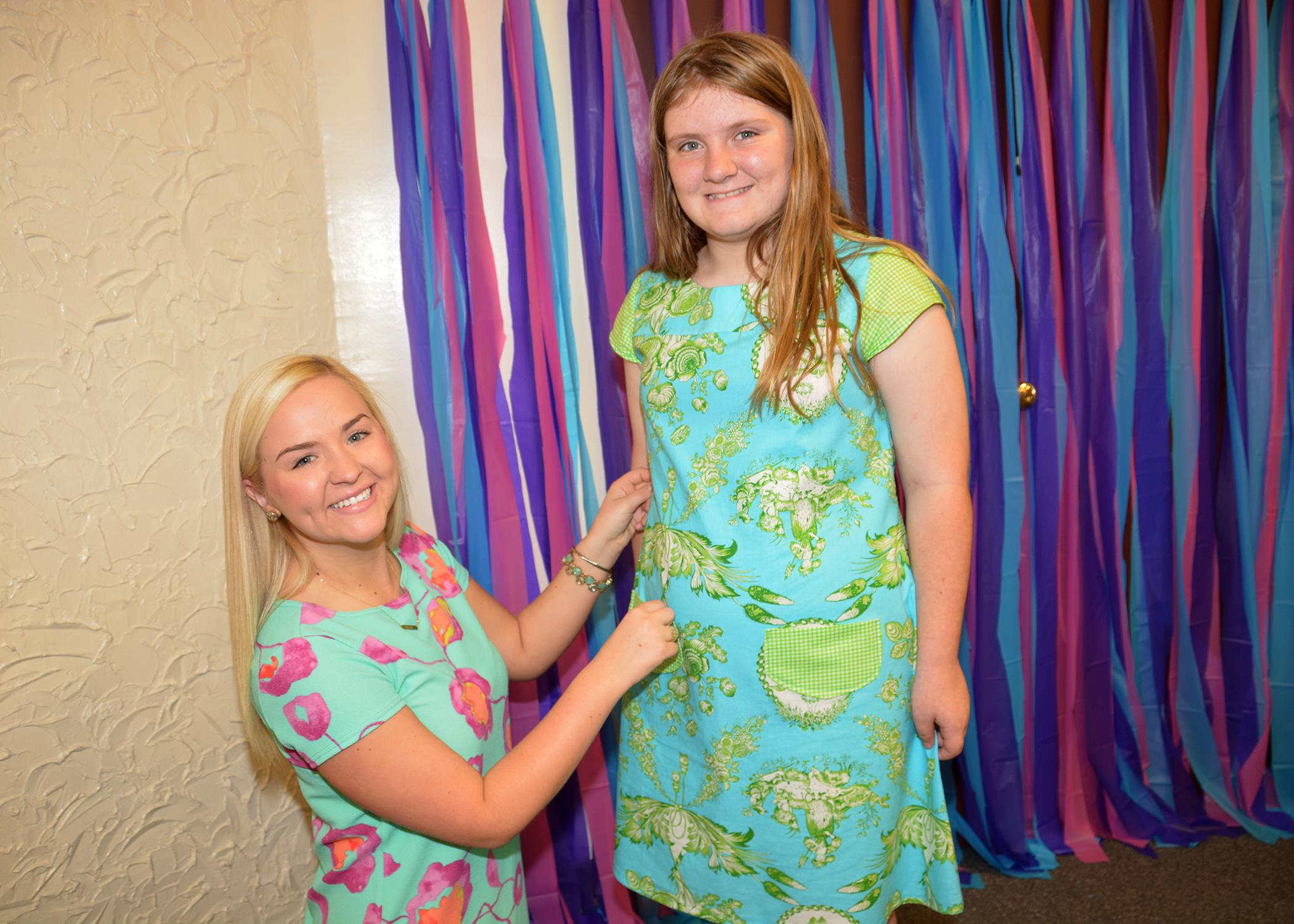 Mississippi State University fashion design and merchandising major Kelsie Bynum of Laurel inspects the dress she constructed for Oktibbeha County 4-H member Cassin Gant before a special fashion show in Starkville, Mississippi, on May 2, 2015. (Photo by MSU Ag Communications/Linda Breazeale)