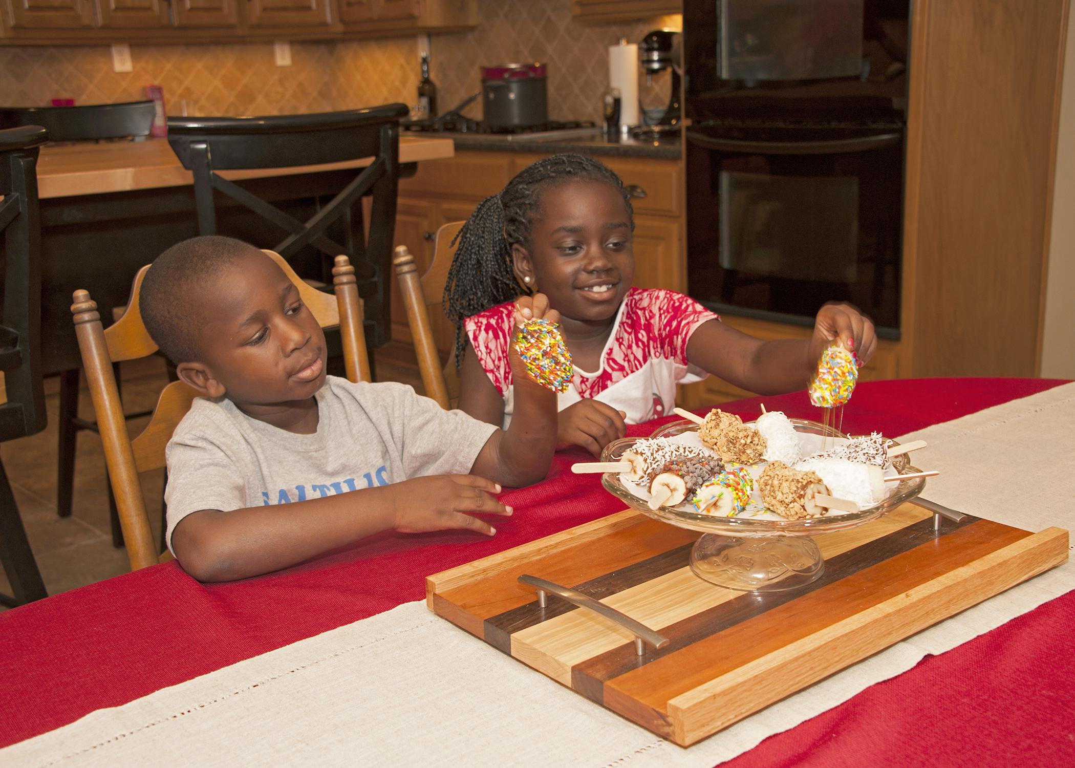 Six-year-old Jordan Ross and 8-year-old Nyema Johnson of Columbus enjoy choosing fun summer treats -- frozen banana pops dipped in either vanilla yogurt or almond bark. (Photo by MSU Ag Communications/Kat Lawrence)