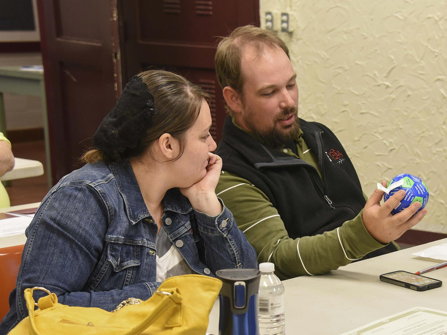 Althea and Joel Bontrager of Columbus examine a communication ball at the beginning of a three-hour workshop for foster/adoptive parents in the Oktibbeha County Extension Office on March 19, 2016. (Photo by MSU Extension Service/Kevin Hudson)