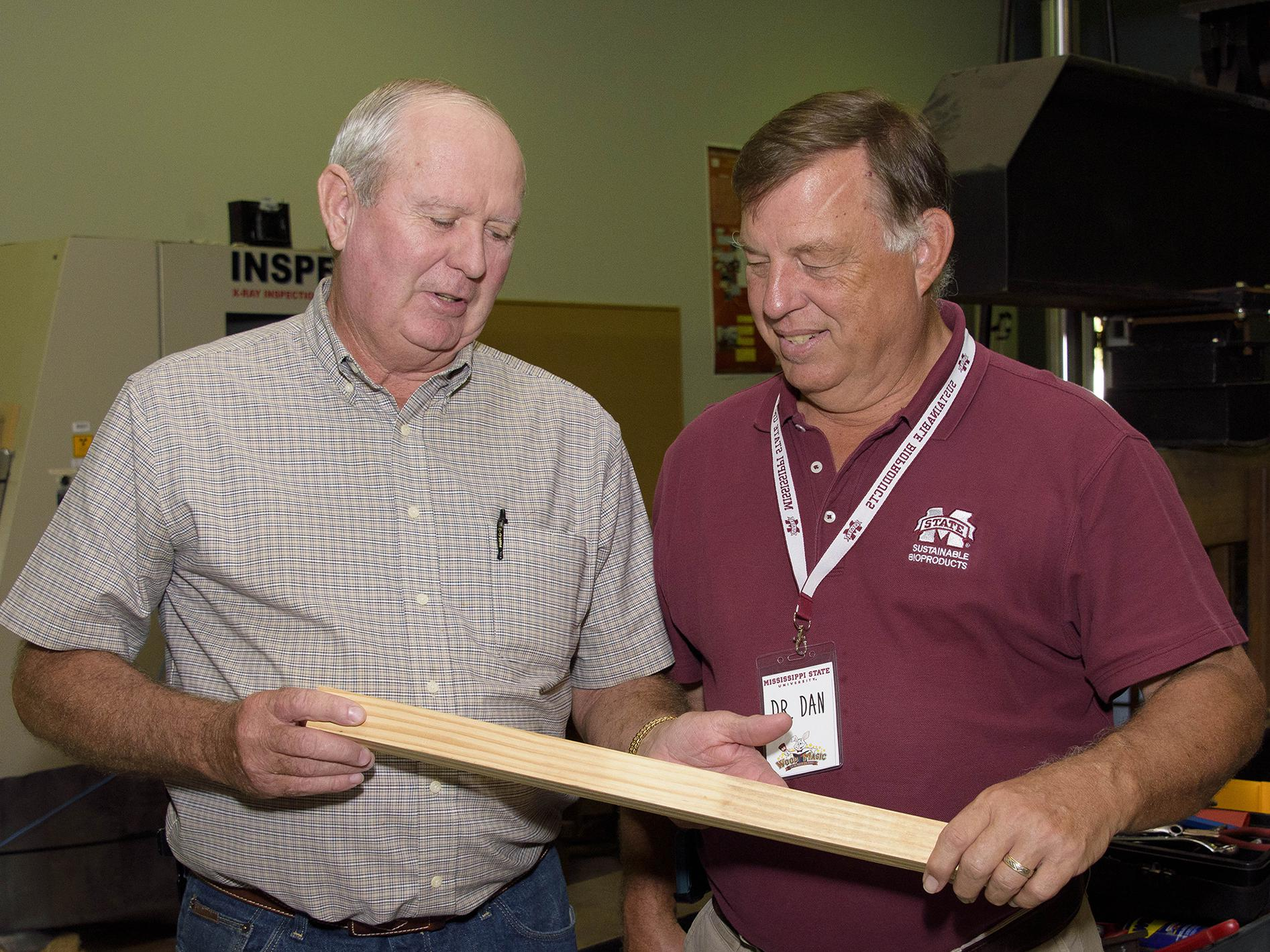 Mississippi Representative Ken Morgan of Marion County, left, examines a wood product held by Dan Seale, a professor of sustainable bioproducts at the R.T. Clapp Forest Products Lab at Mississippi State University. Morgan and other members of Senate and House agricultural committees visited MSU on Oct. 18 and 19, 2016. (Photo by MSU Extension Service/Kevin Hudson)