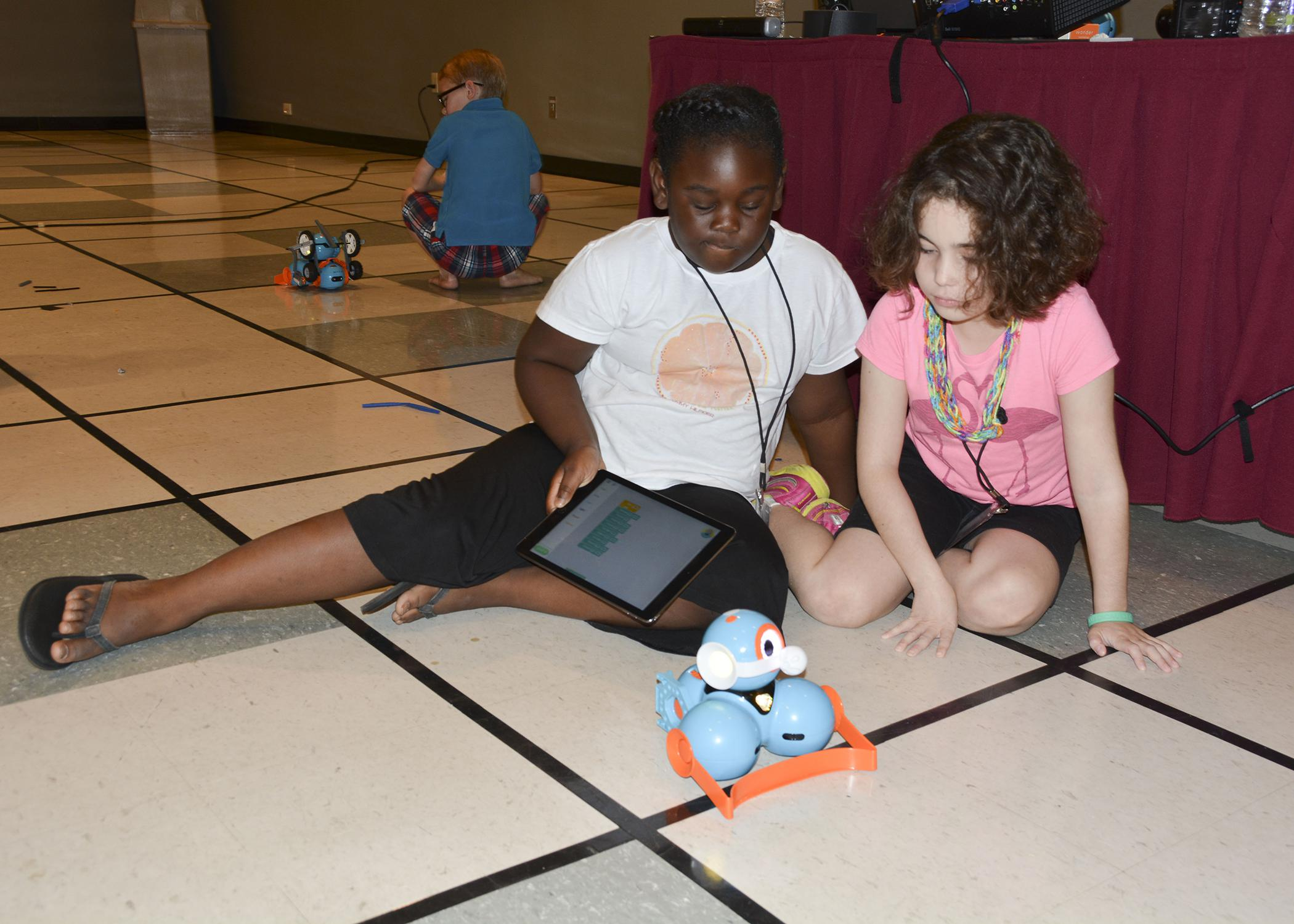 Samyra Harris, left, and Julia Schloemer focus intently on their Dash robot during the 4-H Cloverbud Robotic Camp at Mississippi State University on July 7, 2015. (Photo by MSU Ag Communications/Linda Breazeale)