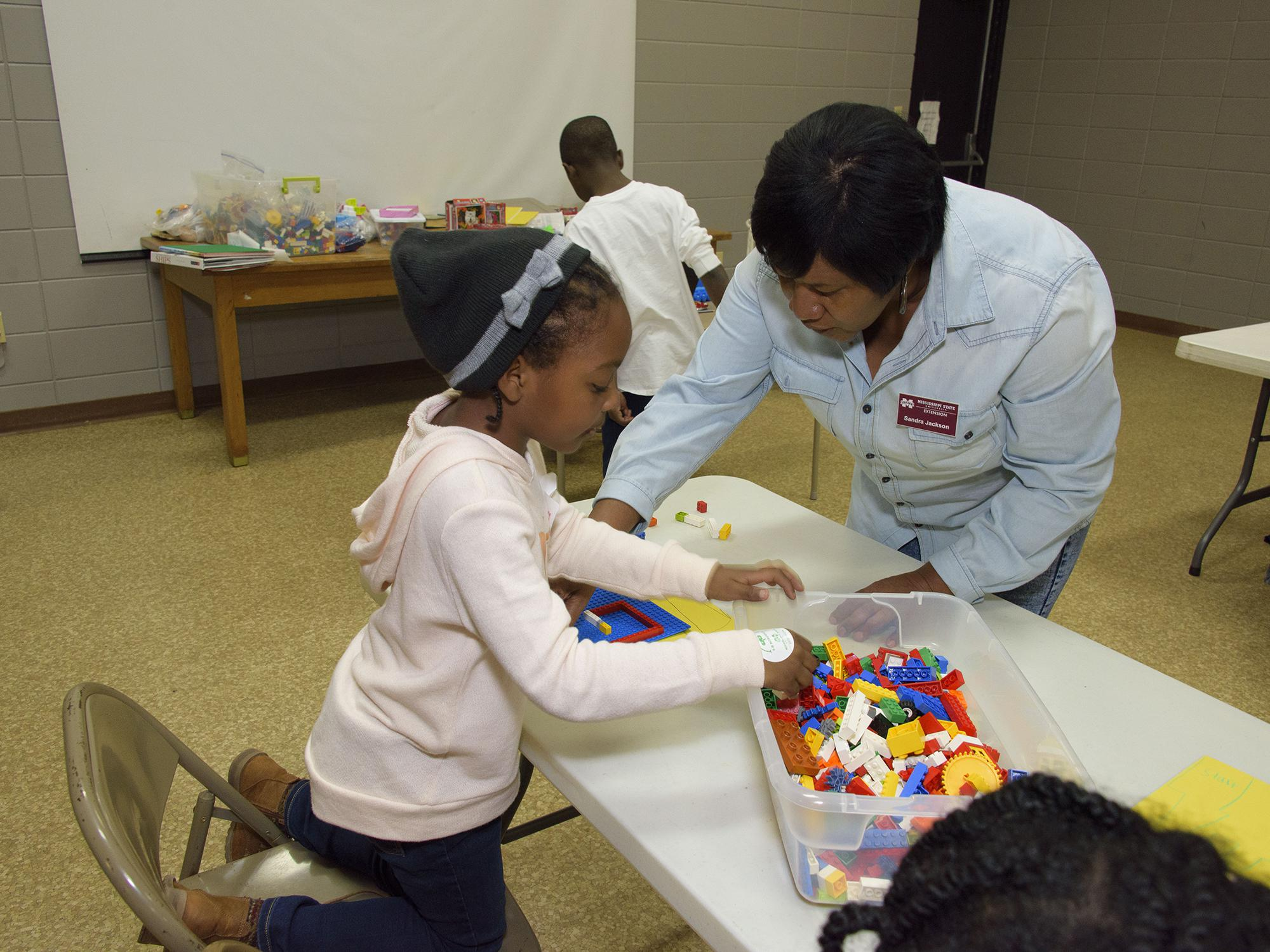 Sandra Jackson, an agent of the Mississippi State University Extension Service in Winston County, helps 6-year-old Akilah Goss assemble a Lego maze March 16, 2017. Jackson was the first agent to teach the 4-H Lego Engineering Club curriculum, which is a STEM program geared toward 4-H'ers aged 5 to 7. (Photo by MSU Extension/Kevin Hudson)
