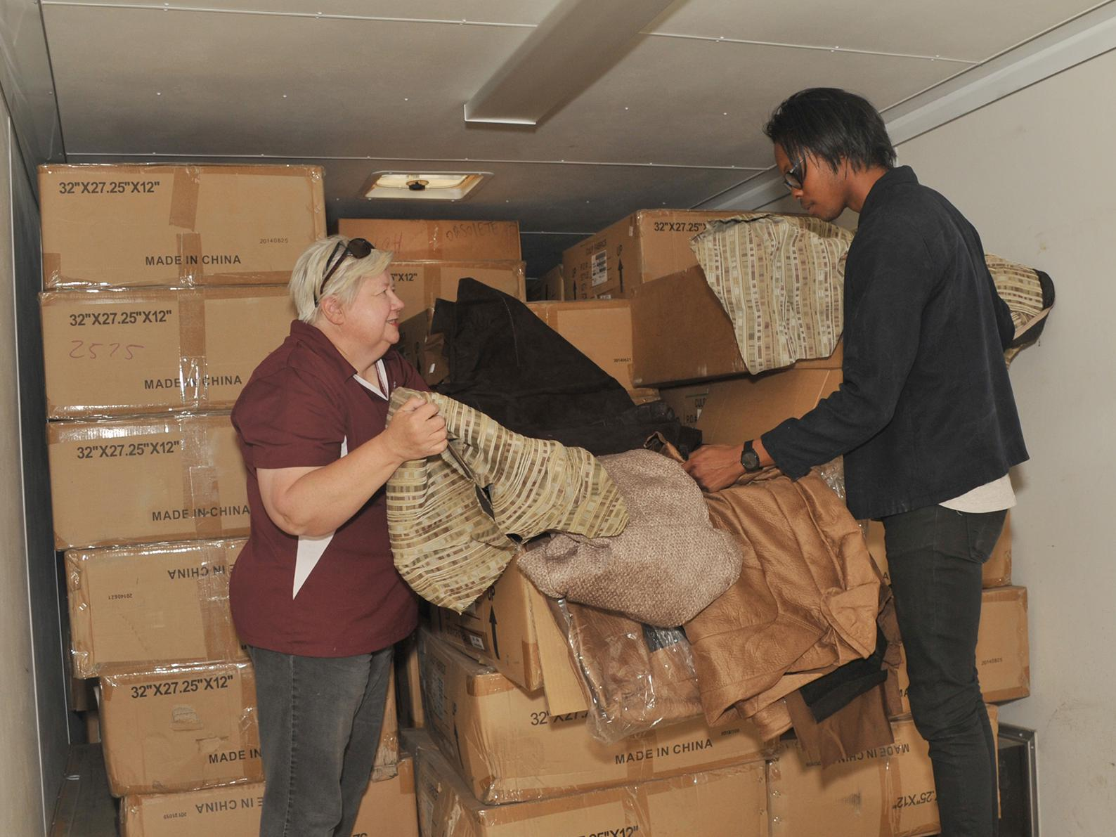 La-Z-Boy Inc. has donated about 130 boxes of discarded upholstery fabric to the Mississippi State University Extension Service. Sylvia Clark, left, an Extension family and consumer sciences associate, and student worker Kamau Bostic unpack the truckload of material March 24, 2017. (Photo by MSU Extension/Kat Lawrence)