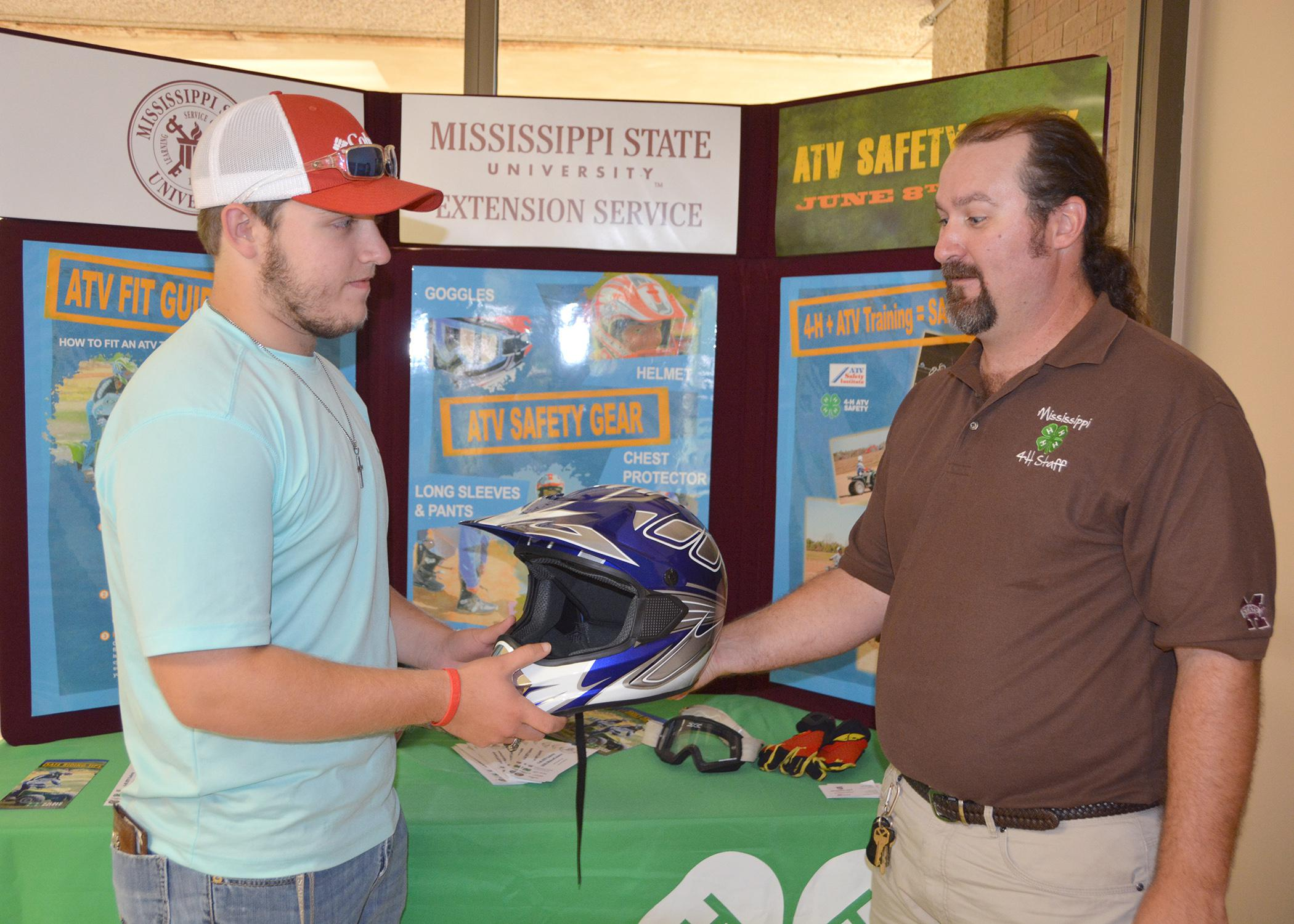 Parker Simpson of Choctaw County, left, talks with all-terrain vehicle safety instructor Brad Staton about the proper gear to wear while riding an ATV, including a helmet, eye protection and gloves. (Photo by MSU Ag Communications/Keri Collins Lewis)