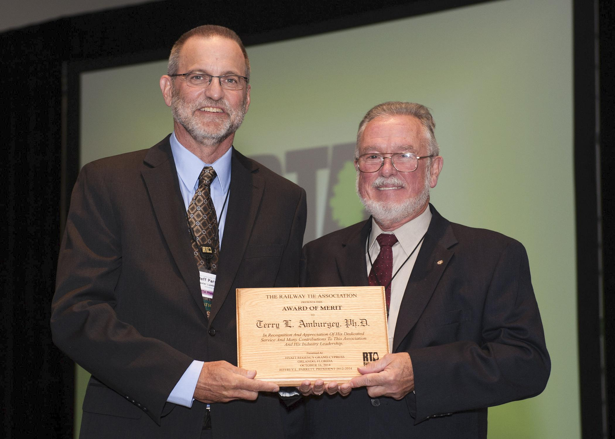 Jeff Parrett, currently of Wheeler Lumber and past president of the Railway Tie Association, left, presents Terry Amburgey, Mississippi State University professor emeritus and Giles Distinguished Professor, with the association's lifetime merit award. (Photo by Gary Coleman/Coleman Photography)