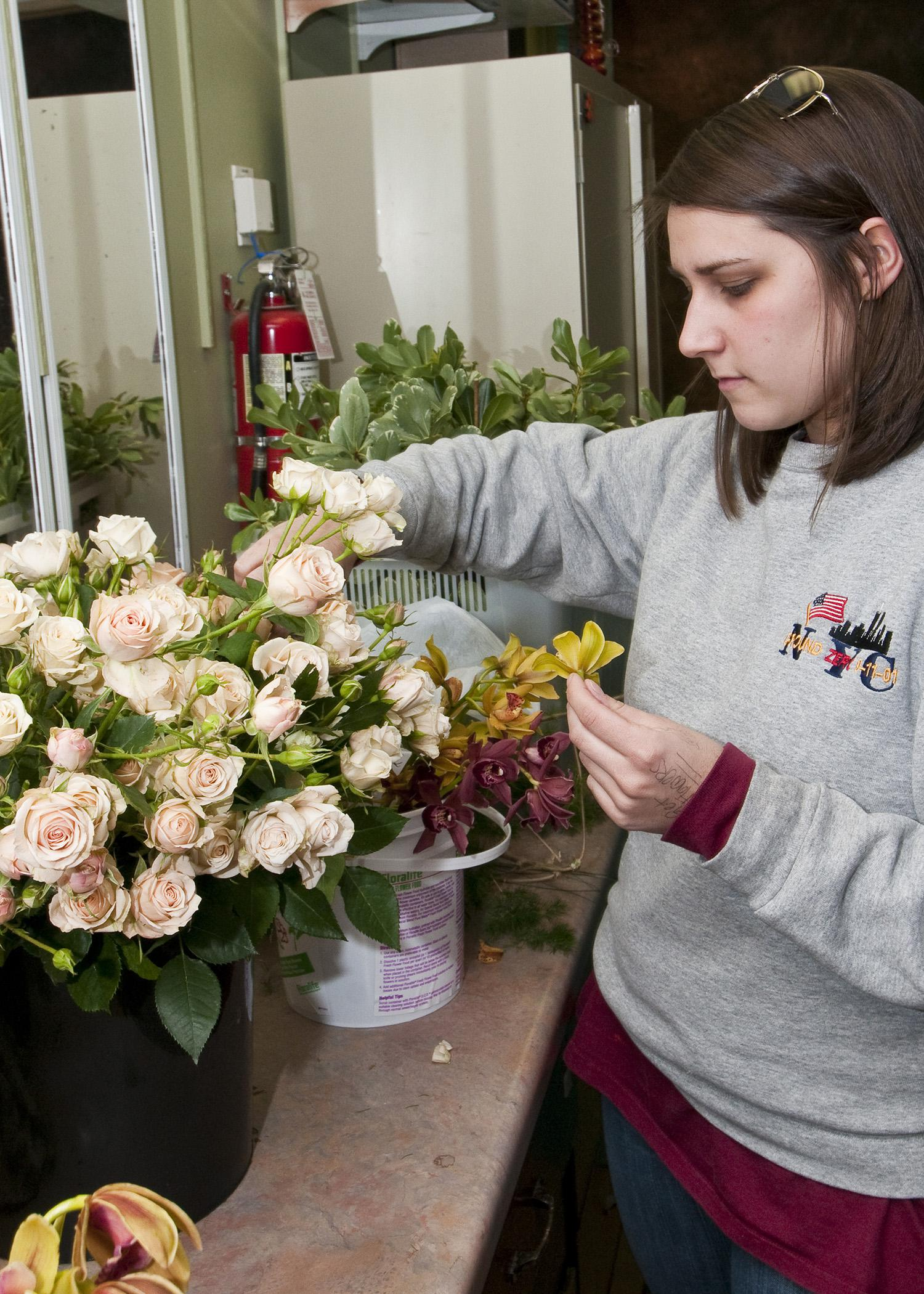 A good florist will help make decisions on what flowers and colors to include in a wedding. Here, Mississippi State University senior Meryl Williams of Columbus selects flowers and foliage for a corsage project in her wedding floral design class. (Photo by MSU Ag Communications/Scott Corey)