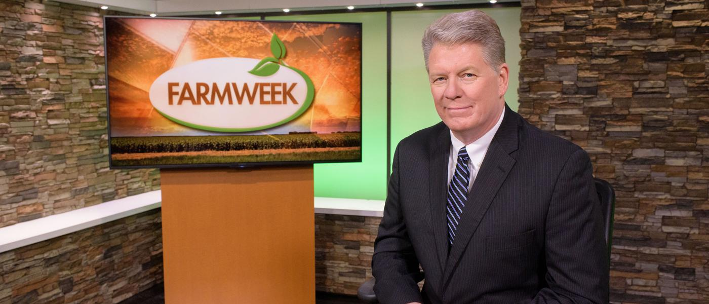 A man sits in TV studio with Farmweek logo on monitor behind him.