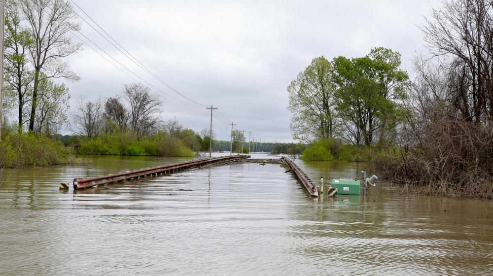 Flood waters have completed covered a road with only the top rails of the bridge visible.