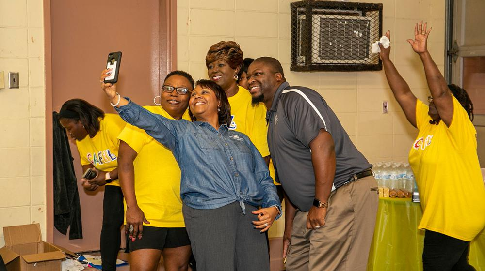 Four members of the Hollandale group Community Action for Healthy Lifestyles take a selfie with Extension agent Alexis Hamilton at the opening of their fitness center.