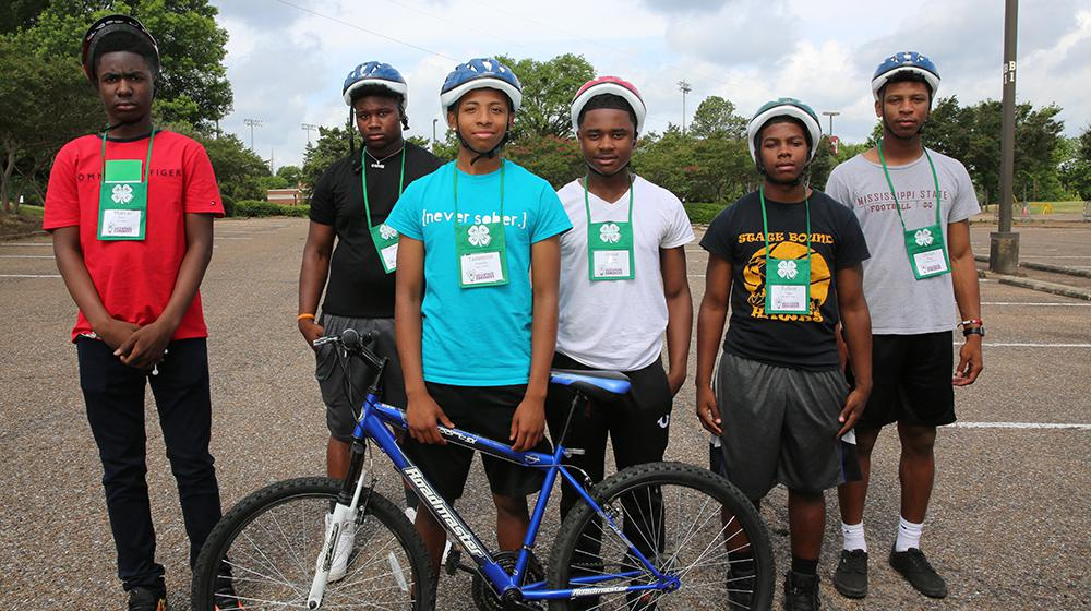 Young men in parking lot with bicycle.