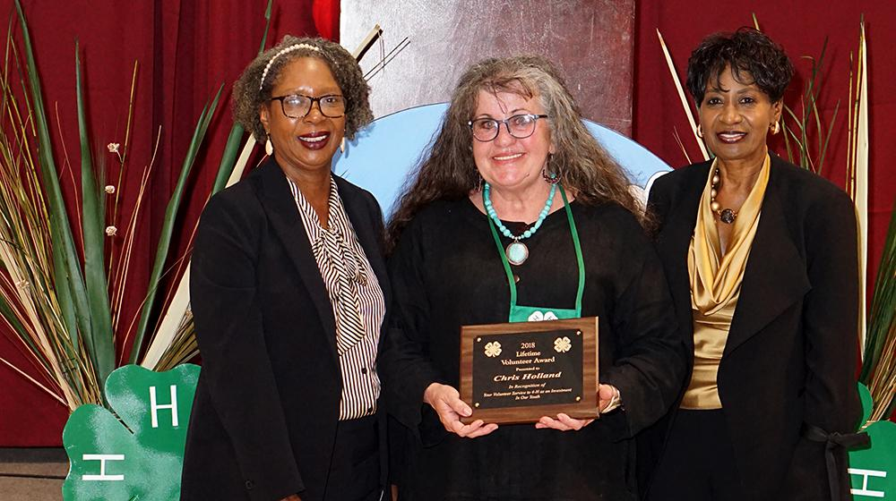 Two women stand beside a woman holding an award.