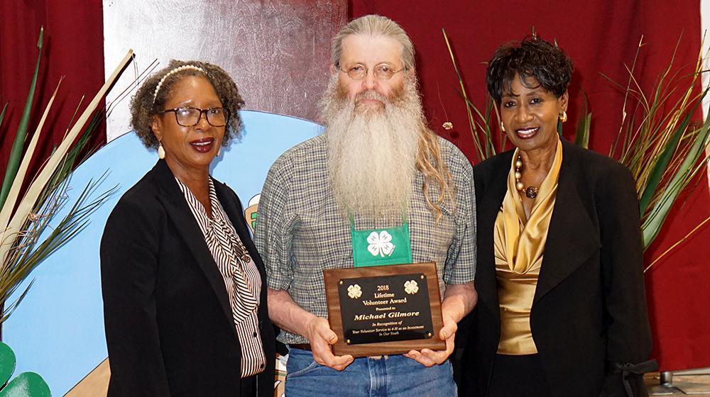 A man holding an award stands between two women.