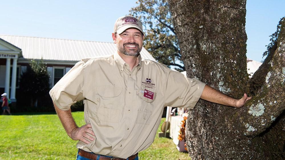 Dr. Eric Stafne, wearing khaki shirt and ball cap, leaning on tree at Fall Flower & Garden Fest.