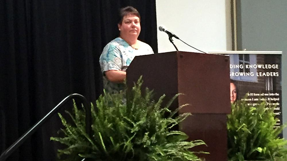 A woman at podium giving welcome and introductions at conference.