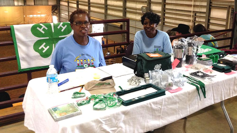Two women sitting at a table filled with 4-H items for sale NE horse show and MVLA Store.