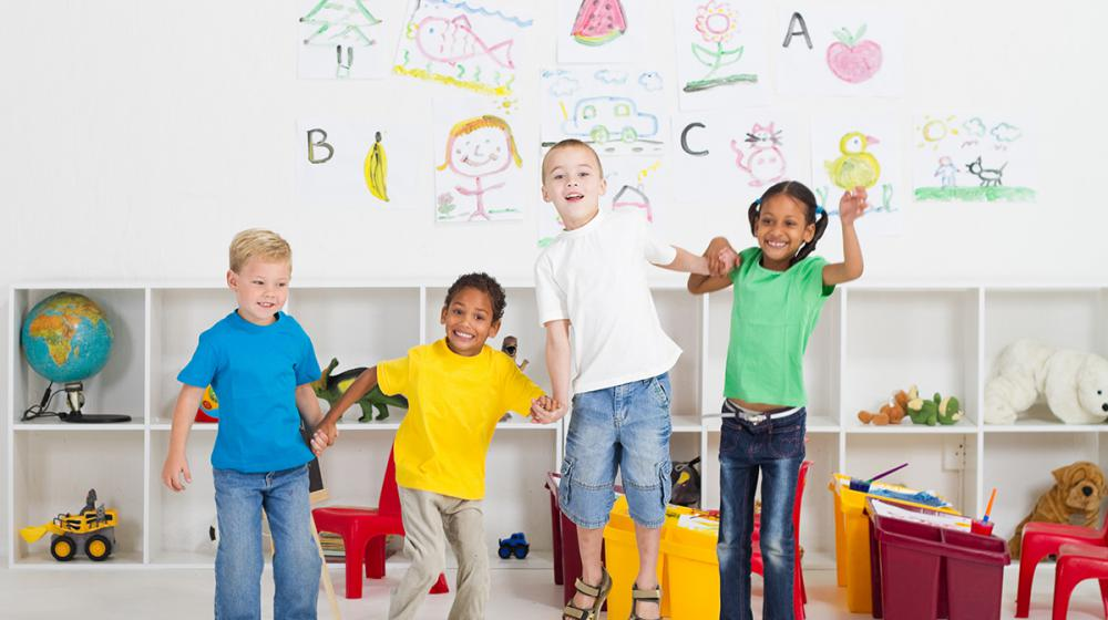 4 young children standing in a classroom, holding hands and jumping.