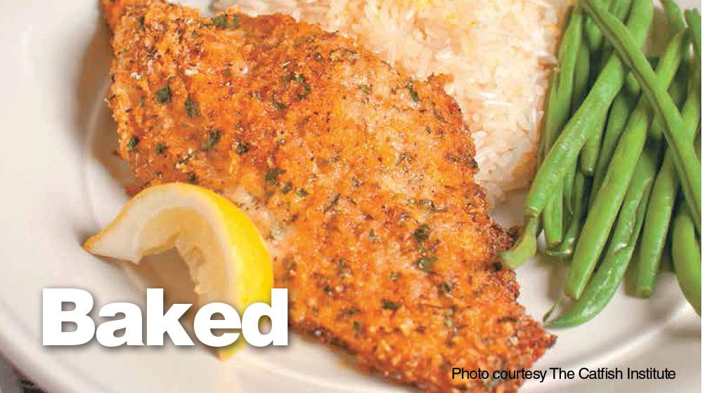 Close-up photo of baked, breaded catfish served on a plate with white rice, green beans and a slice of lemon