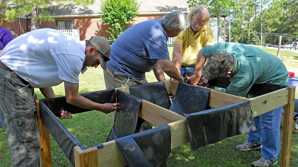 From left, Lamar County Extension Agent Ross Sadler, Pine Belt Master Gardener Paul Cavanaugh, Lamar County Technical Center teacher and volunteer Ken McCoy and Pine Belt Master Gardener intern Cecil Chambliss prepare a handicapped-accessible raised bed for plants. The group built two beds for residents of The Windham House of Hattiesburg, an assisted-living facility for seniors on May 28 and will return monthly to help with the beds and teach workshops. (Photo by MSU Ag Communications/Susan Collins-Smith)