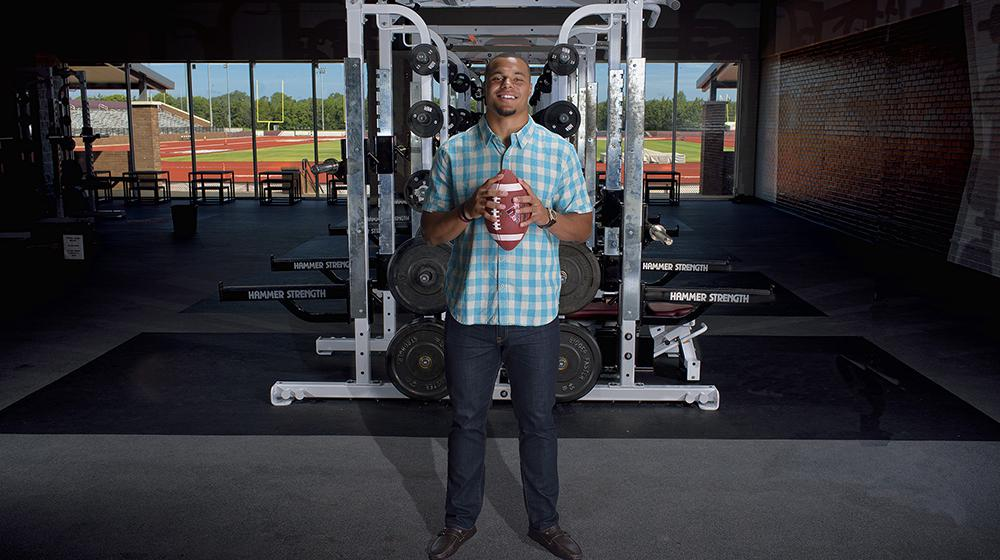 Dak holding football in front of weights during the during the Colon Cancer Screening PSA shoot.