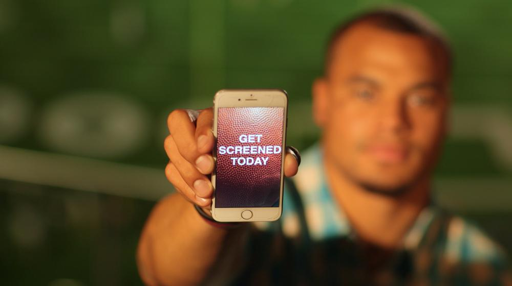 "Dak holding phone with message ""Get screened today"" during the Colon Cancer Screening PSA shoot."