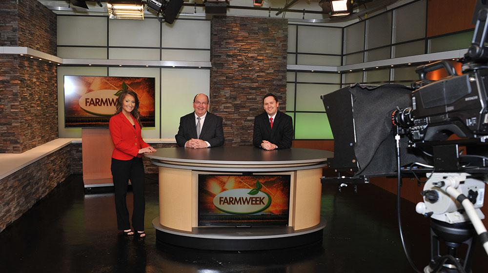 a woman and 2 men at the anchor desk in the Farmweek TV studio.