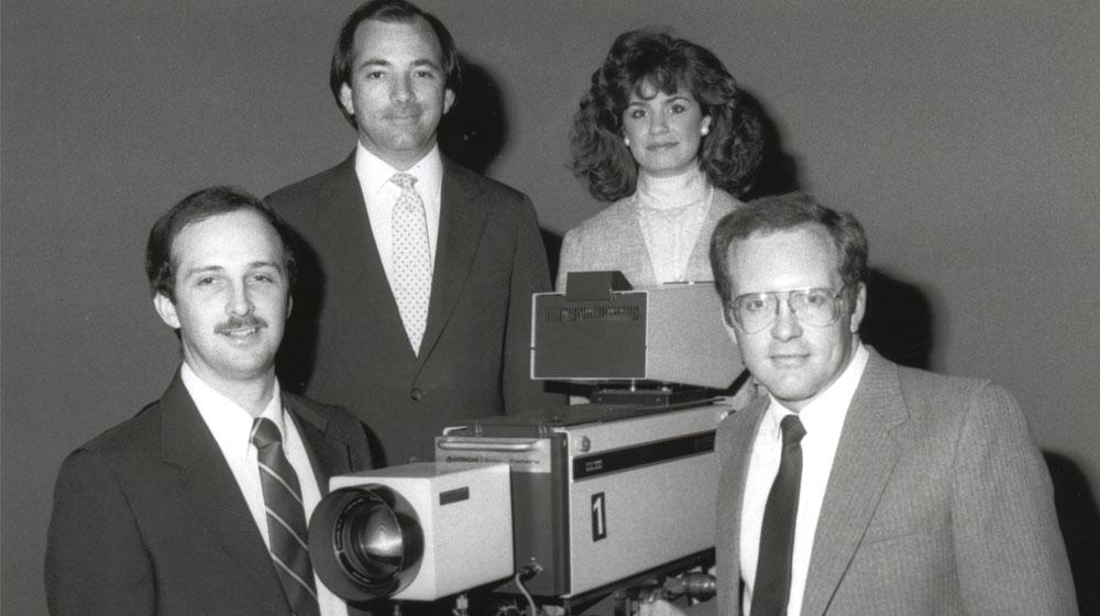 News crew, 3 men and a woman, posed around an old television camera.