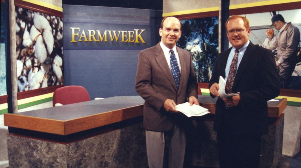 2 male anchors in front of Farmweek TV studio desk