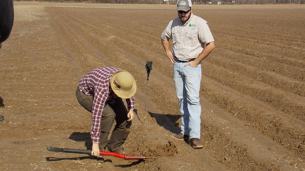 Woman using shovel in field to get soil sample while man looks on.