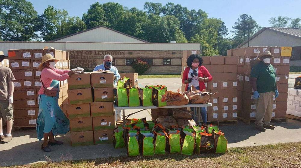 Four people work at a food pantry in front of the Lexington Multi-Purpose Complex. They are standing around a table, surrounded by many boxes and tote bags with food in them.