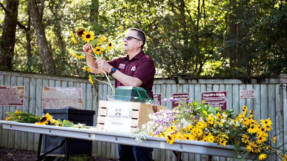 Outdoor exhibitor with table and cut flowers at Fall Flower & Garden Fest.