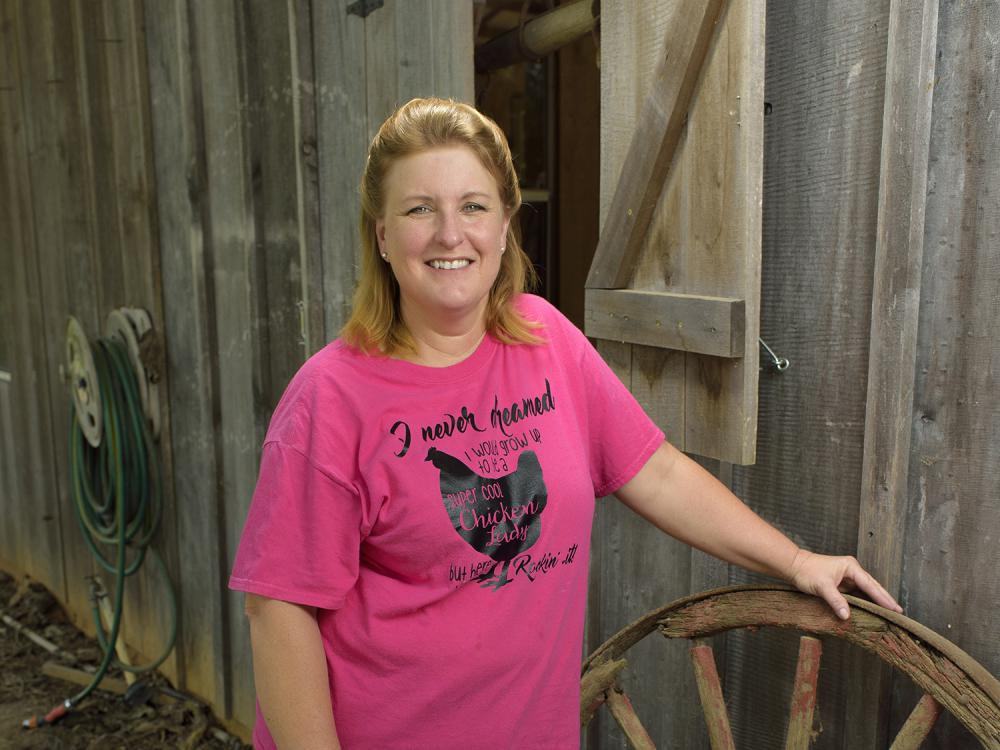 Dressed in a pink T-shirt and blue jeans, broiler grower Teresa Dyess stands next to two wagon wheels in front of a barn on her family farm.
