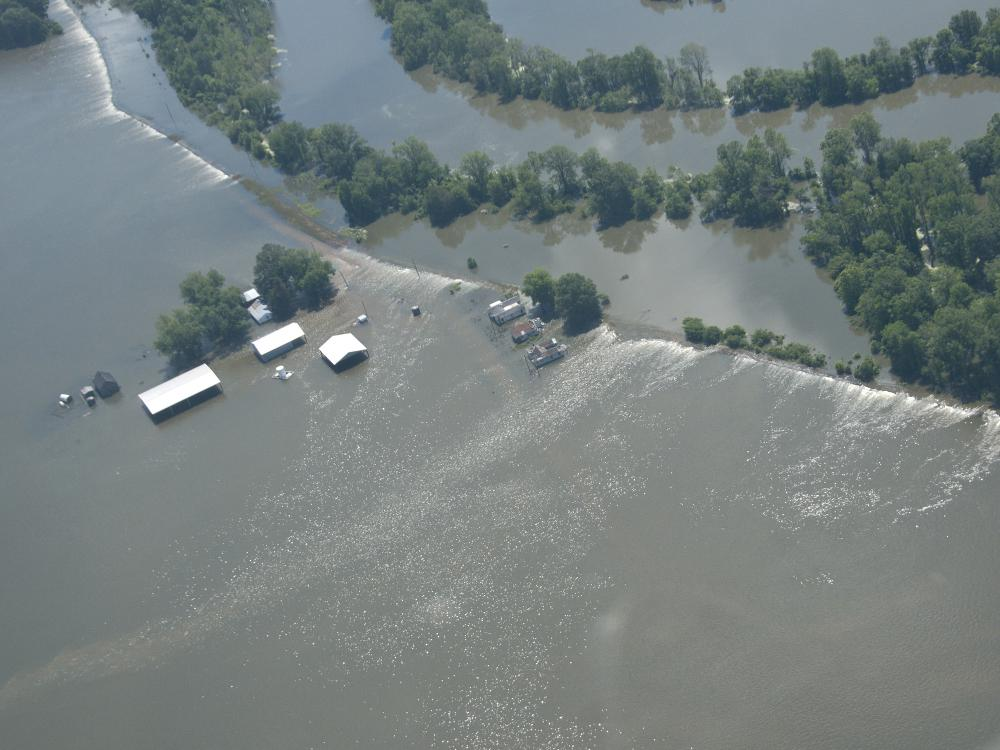 View from an airplane flying over extensive flood waters flowing over a levee and surrounding homes, farm buildings and crops.