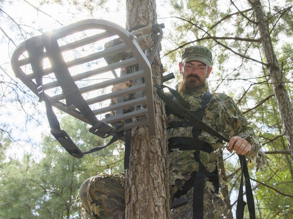Hunter wearing camouflage secures a portable platform to the side of a tree.