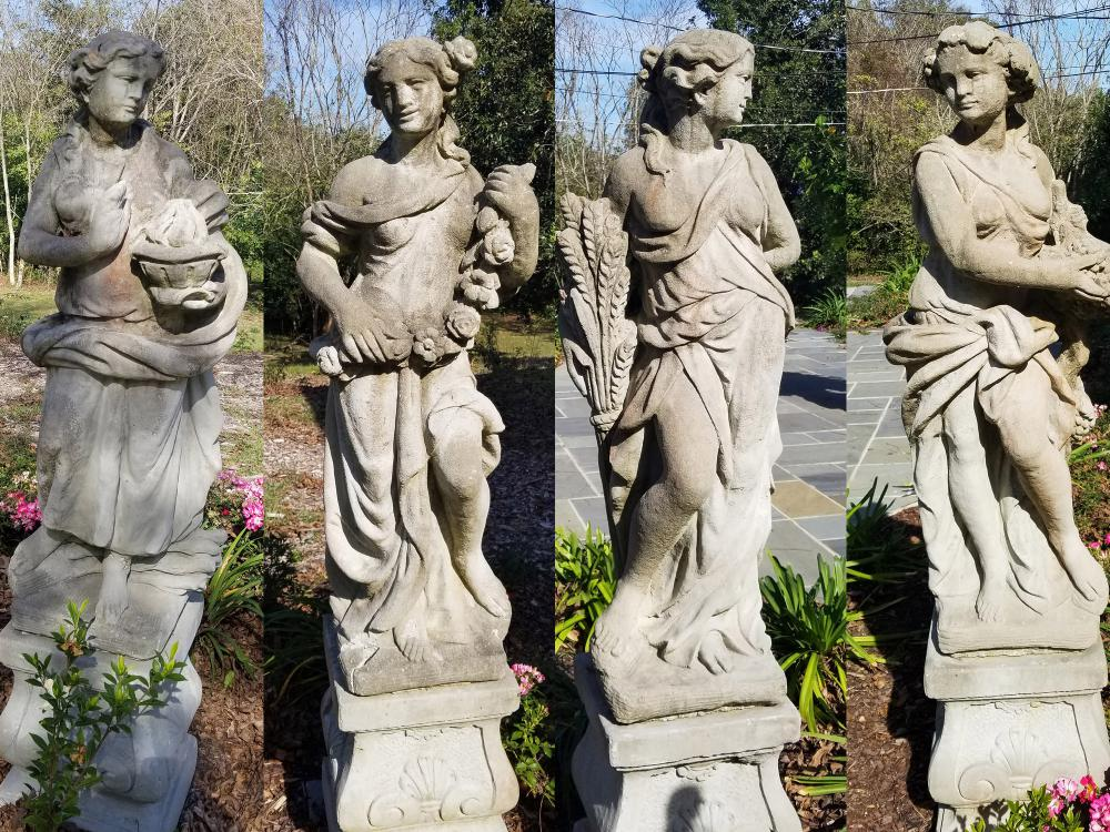 Four stone statues are seen representing ancient Greek goddesses.