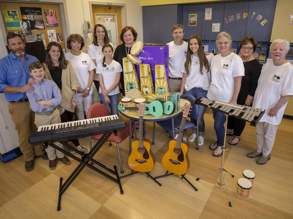 A group of people surround more than 20 musical instruments.