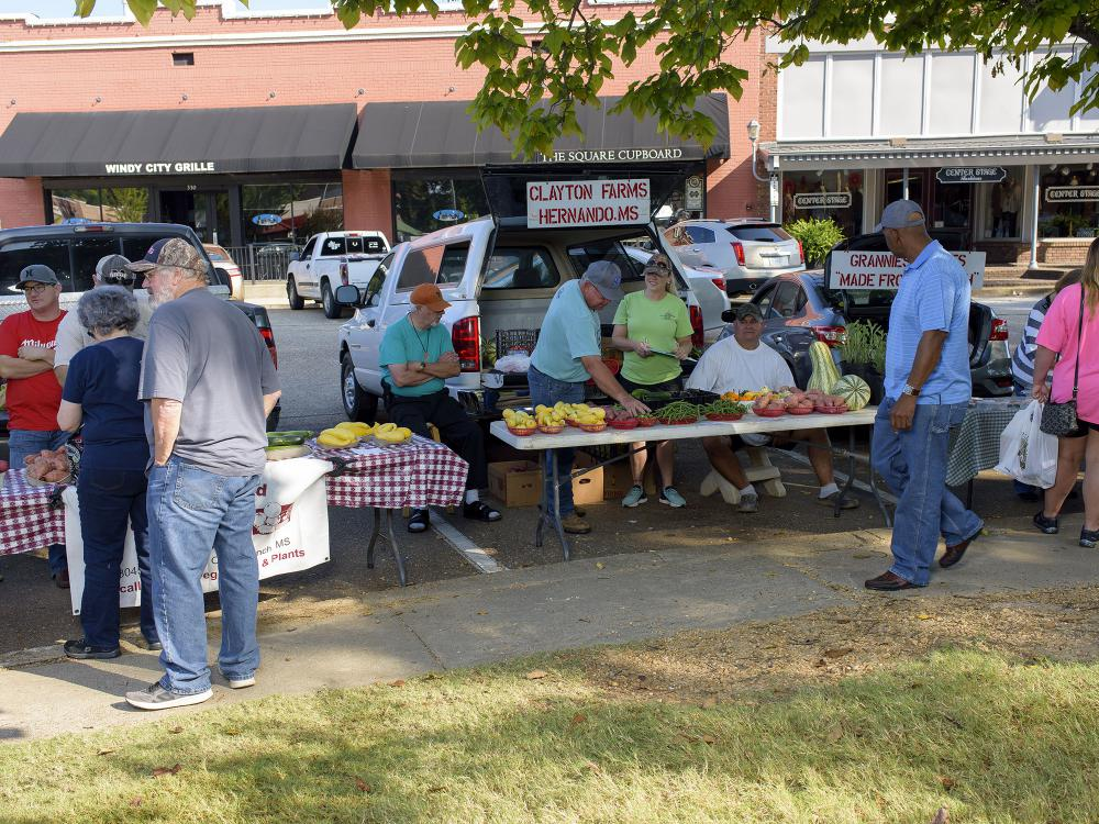 Several people gather to buy produce on display at a farmers market.