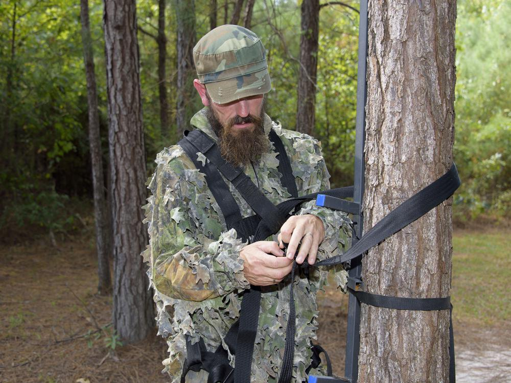 Man standing in the woods inspects nylon straps on a tree stand he is holding on in his hands.