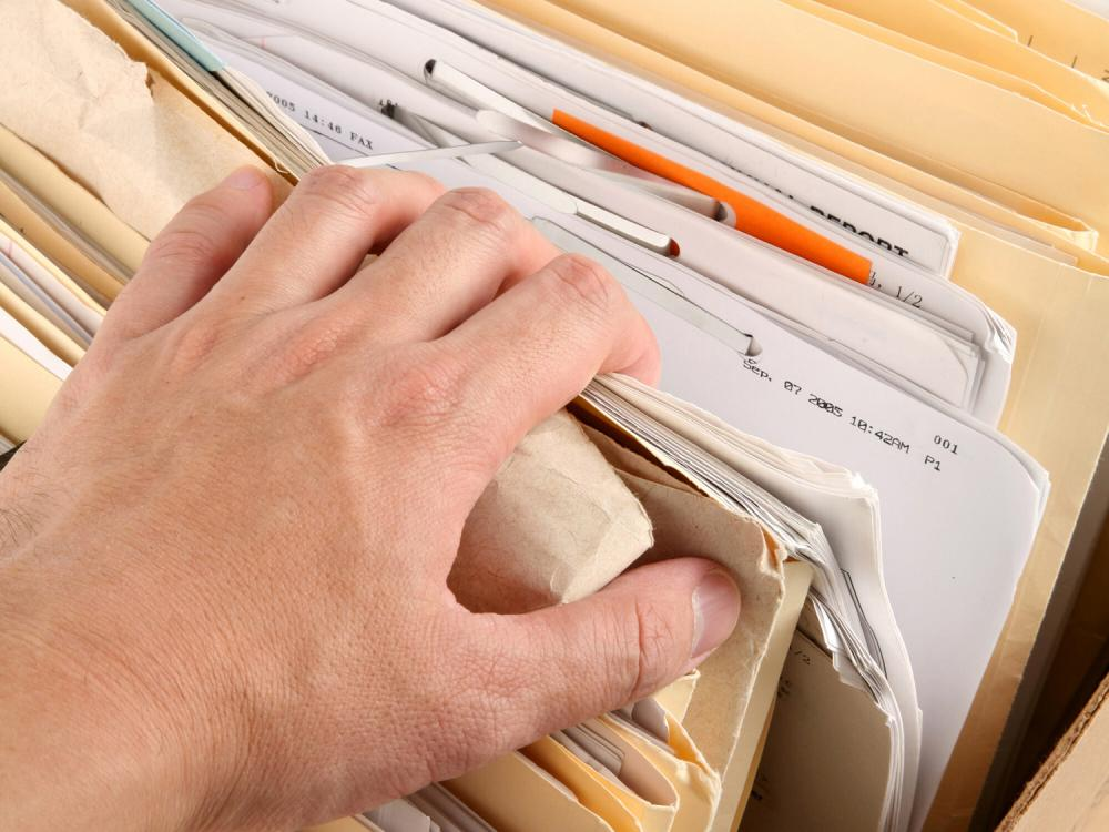 A man's hand reaches into a box of files, pulling back the corner of one folder.